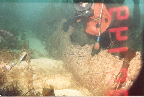 The diver is holding onto a piece of the wooden hull.(Sorry about the time stamp)